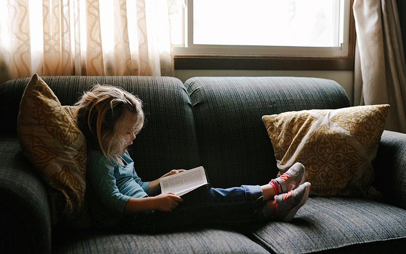 niña leyendo libro tumbada en un sofá