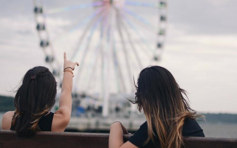 Dos mujeres sentadas en un banco mirando una noria